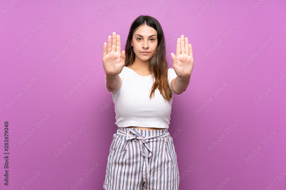 Fototapety, obrazy: Young woman over isolated purple background making stop gesture and disappointed