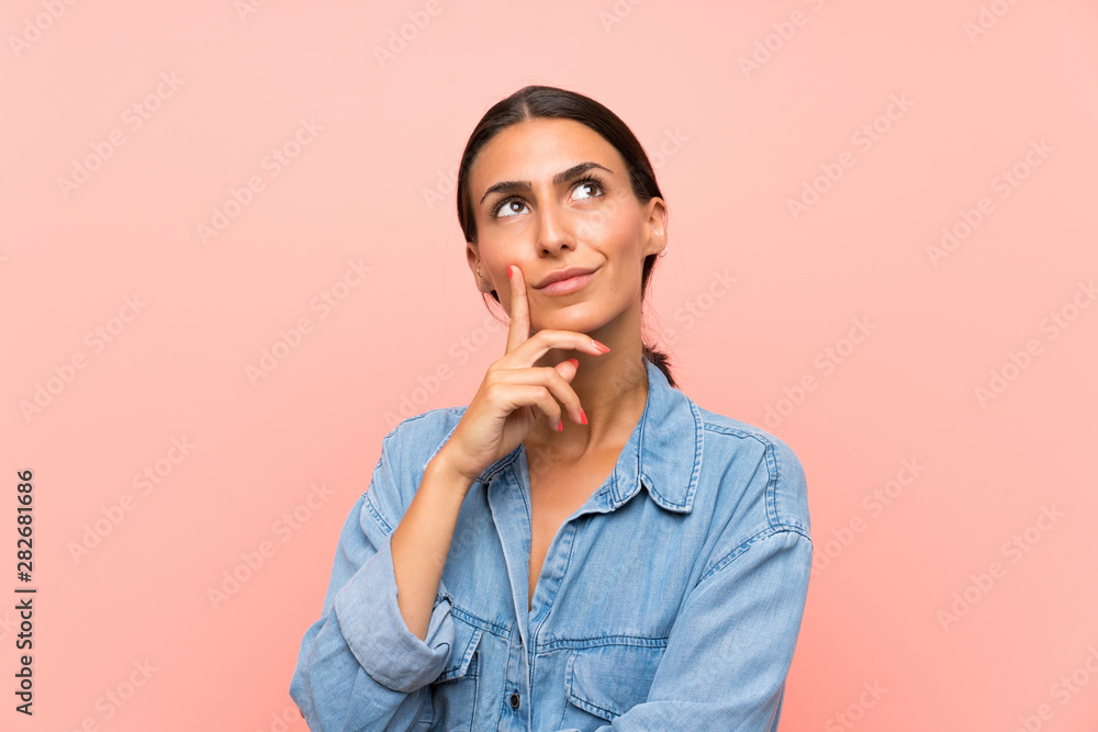 Fototapeta Young woman over isolated pink background thinking an idea