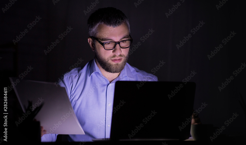 Fototapeta Caucasian man is working with papers, using laptop