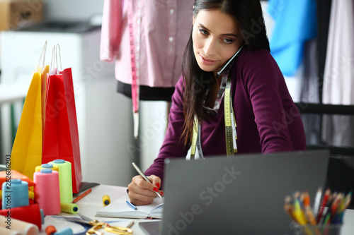 Poster Individuel Adult caucasian beauty businesswoman takes an order by phone looks at laptop screen and makes notes in notebook an office background. Delivery and tailoring clothes concept.
