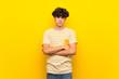 Young man over isolated yellow wall feeling upset