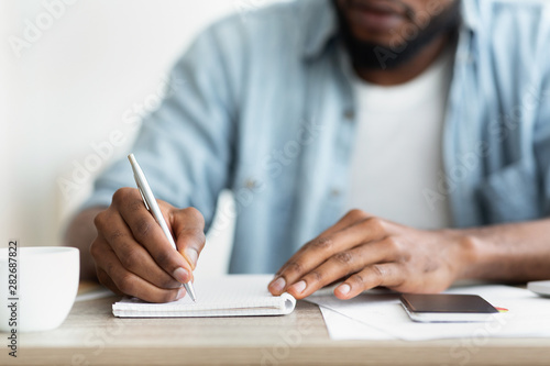 African american businessman writing down his plans to notepad Fototapete