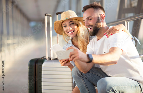 Foto  Couple using phone, making video call in airport