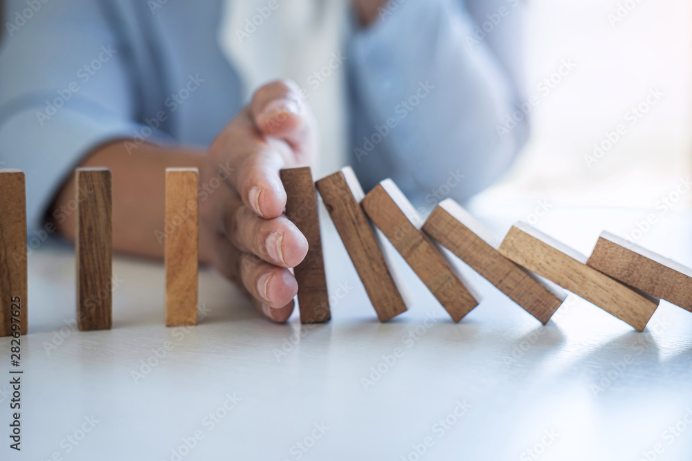 Fototapeta Risk and Strategy in Business, Image of hand stopping falling collapse wooden block dominoes effect from continuous toppled block, prevention and development to stability