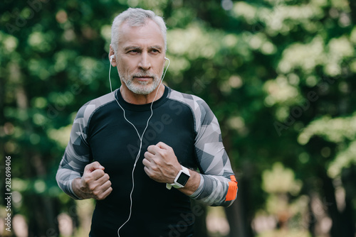 Fotografia handsome mature sportsman listening music in earphones while running in park