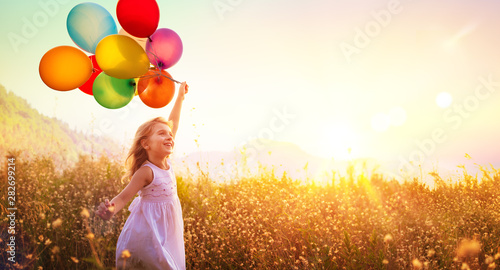 Fototapeta Happy Child Running With Balloons In Field At Sunset obraz