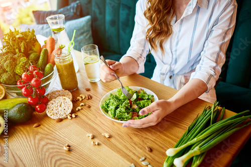 Young happy woman eating salad in the beautiful interior with green flowers on the background and fresh ingredients on the table. Healthy food concept