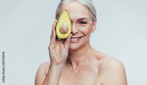 Senior woman with a half avocado - 282710246