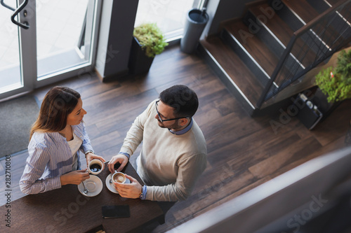 Couple in a coffee shop having a conversation Canvas Print