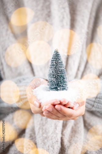 Christmas decor in women hand. Christmas greeting card. Woman's hands hold christmas or new year decorated gift.
