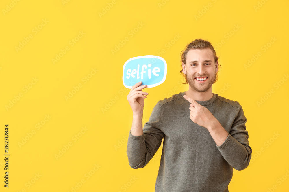 Fototapety, obrazy: Male blogger holding paper with text SELFIE on color background