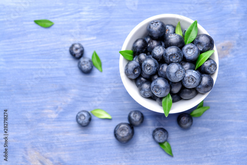 Fototapeta Bowl with ripe blueberry on wooden background obraz