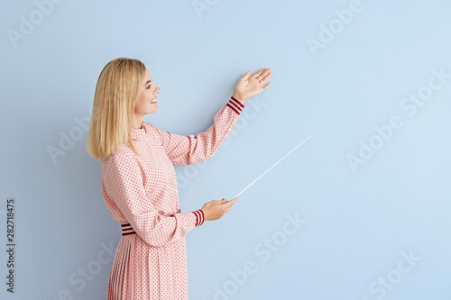 Fotografie, Obraz Beautiful female teacher with pointer on color background