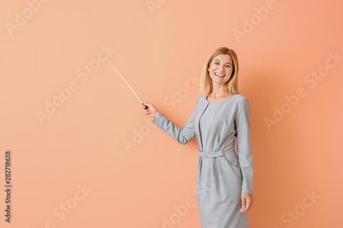 Obraz na płótnie Beautiful female teacher with pointer on color background