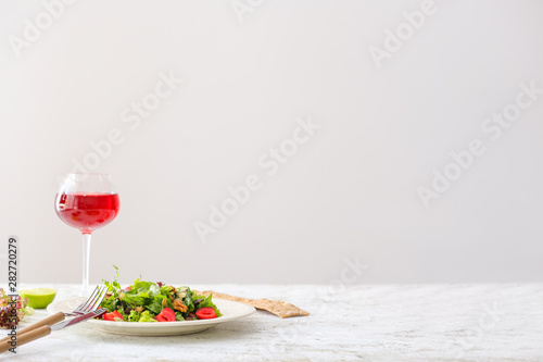 Foto auf Leinwand Alkohol Plate with fresh tasty salad and glass of drink on table