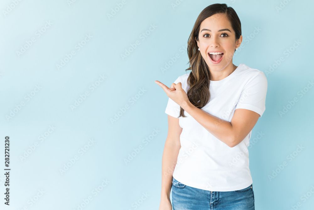 Fototapeta Attractive Female Gesturing Over Plain Background