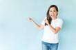 Leinwandbild Motiv Cheerful Woman Pointing Against Isolated Background