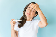 Unwell Woman Checking Body Temperature In Studio