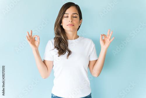 Beautiful Woman Meditating Peacefully In Studio