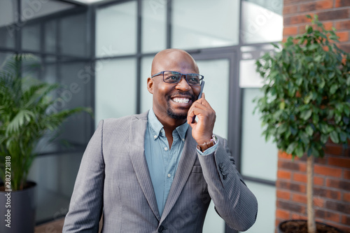 Businessman smiling while speaking by phone with wife