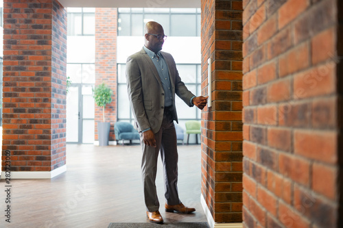 Young businessman wearing glasses standing near elevator