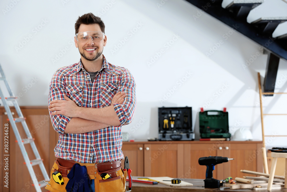 Fototapeta Handsome working man indoors, space for text. Home repair
