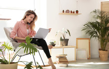 Young Woman Using Laptop At Home, Space For Text. Trendy Room Interior With Plants