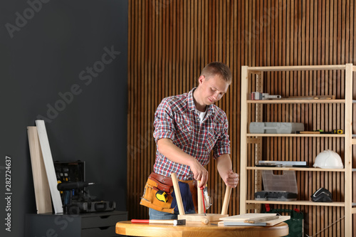 Excellent Handsome Young Working Man Repairing Wooden Stool Using Ocoug Best Dining Table And Chair Ideas Images Ocougorg