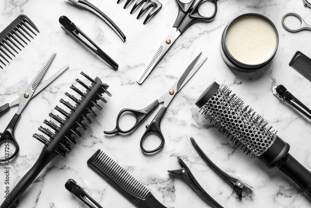 Fototapeta Flat lay composition with scissors and other hairdresser's accessories on white marble background