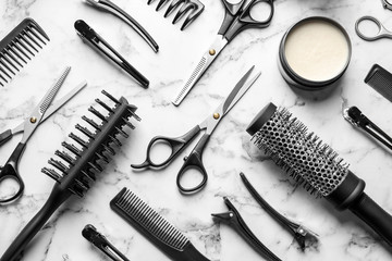 Flat lay composition with scissors and other hairdresser's accessories on white marble background