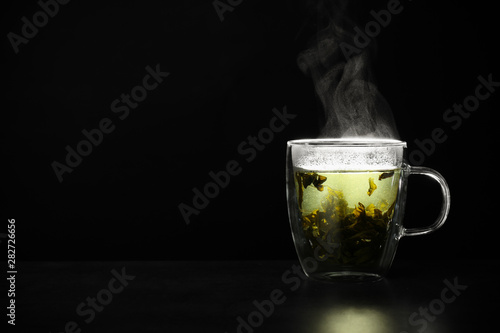 Recess Fitting Tea Glass cup of hot green tea on table against black background, space for text