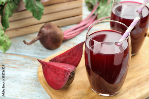 Foto auf AluDibond Orte in Europa Wooden board with cut beet and glasses of juice on table. Space for text