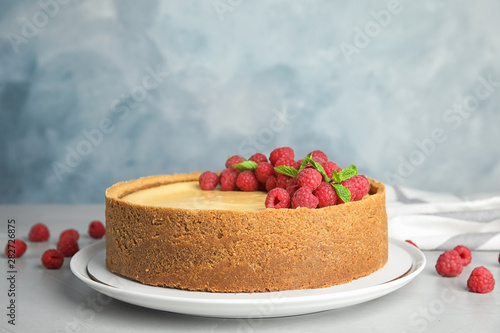 Dessert plate with delicious raspberry cake on table against blue background Canvas Print