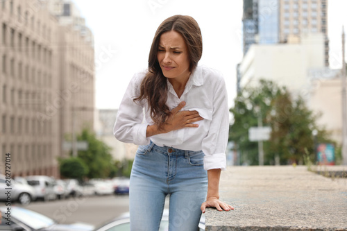 Young woman having heart attack on city street Fototapeta