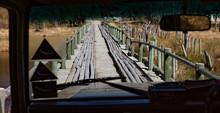 Car Approaches A Crude Wooden Bridge To Cross A River