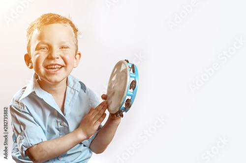 Valokuvatapetti a cheerful boy in a blue shirt holding a tambourine and smiling on a light backg