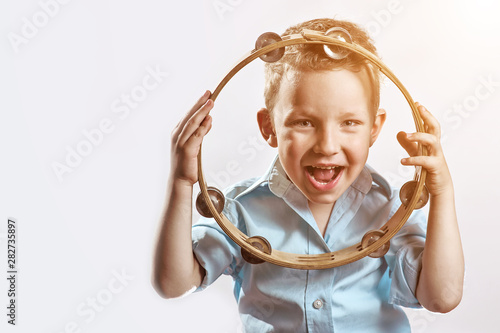 Valokuva  a cheerful boy in a blue shirt holding a tambourine and smiling on a light backg