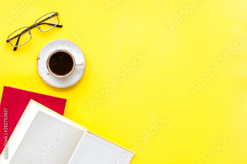 Fotografia, Obraz  Books on library desk for reading, coffee, glasses on yellow background top view