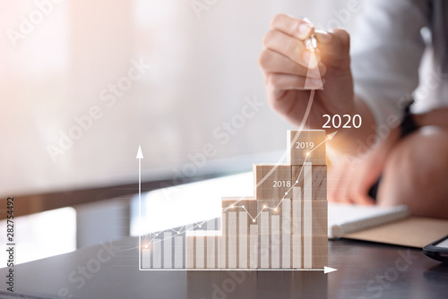 Fotomural  woman use pen plans to increase business growth and an increase in the indicators of positive growth in 2020 on virtual screen