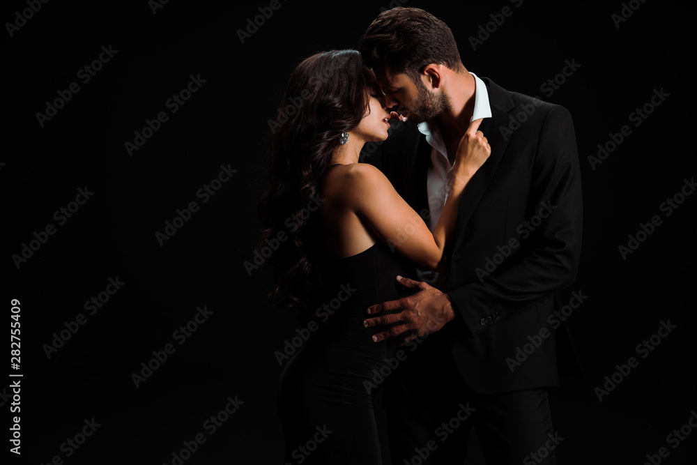 Fototapety, obrazy: attractive girl touching suit of passionate bearded man isolated on black