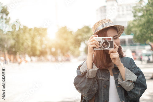 Foto  Smiling woman traveler with backpack holding vintage camera on holiday in thapae