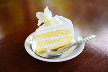 Cake Slice On White Palte With Flower On Wooden Table Background - Delicious Coconut Cake And Spoon