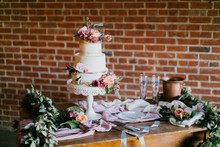 White Wedding Cake With Pink Flowers, Peonies, Garland On Table, Greenery, Copy Space