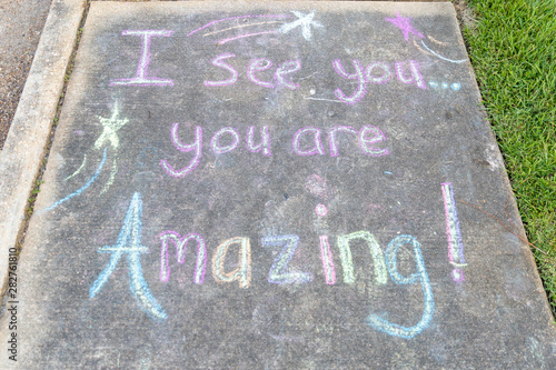 "the words ""I See You, You are Amazing"" written with sidewalk chalk on gray concrete pavement background"