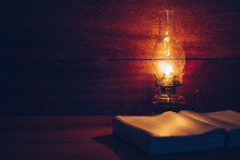 Close Up Of Oil Lamp With Blurred Holy Bible On Wood Table In Dark Room, Bible Study Or Vintage Book Concept