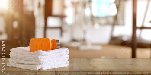 Towels and orange sport bottle with gym background Obraz na płótnie