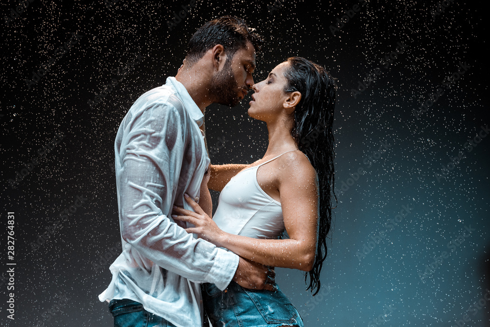 Fototapety, obrazy: side view of handsome man kissing sexy wet girlfriend under raindrops on black