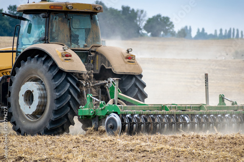 Fotomural  Tractor cultivating the field