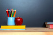Back to school concept. Red apple, colourful pencils and books on blackboard background.