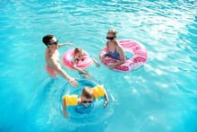 Happy Family Swimming In Pool On Summer Day